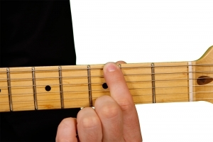Image of finger in wrong place on guitar fretboard