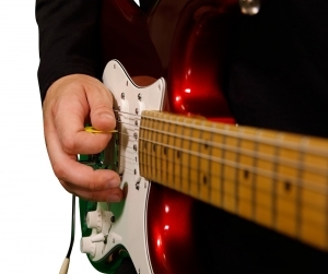 Close up image of guitar player's picking hand
